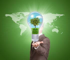 Businessman in a suit hold bulb with tree