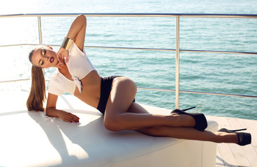 sexy girl with dark hair relaxing on yacht
