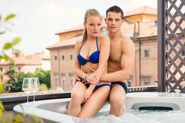 Portrait of a happy young couple enjoying swimming pool.