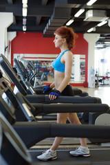 Pretty tall woman exercising on treadmill