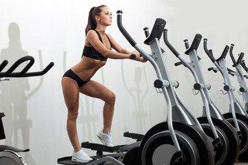 Beautiful young woman exercising on ski simulator