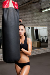 Tanned athlete looks out from behind punching bag
