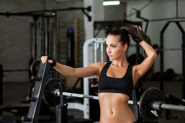 Charming female athlete posing in gym