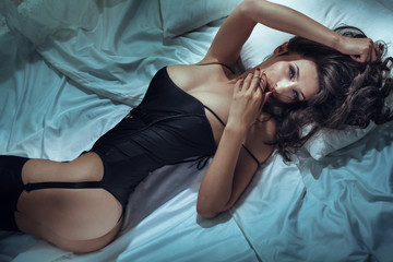 Sexy attractive woman posing in bed