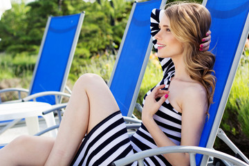 Beautiful woman is resting on the deck chair