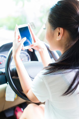 Asian woman texting while driving car