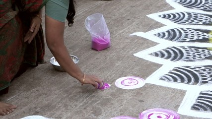 The woman is doing on the asphalt one design of rangoli