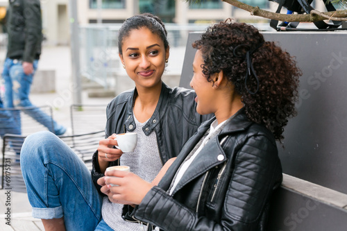 canvas print picture Best friends drinking coffee in city
