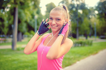 happy fitness blonde athlete listening to music and working out