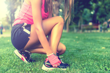 Close-up of active jogging female runner, preparing shoes