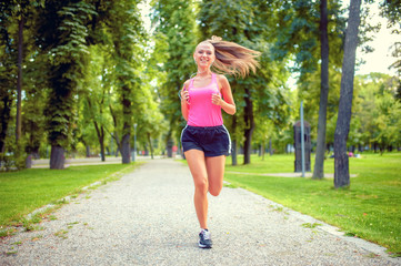 healthy and happy woman running in urban park with headphones