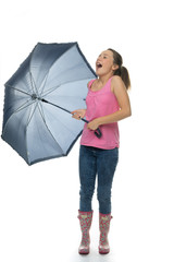 Young girl with an umbrella standing laughing