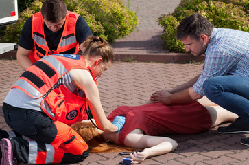 Couple of paramedics examining woman