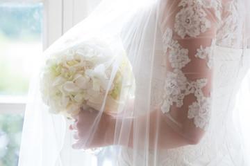 Brautkleid mit Schleier und Brautstrauß