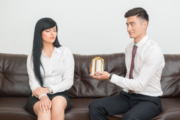Business couple sitting on sofa in office