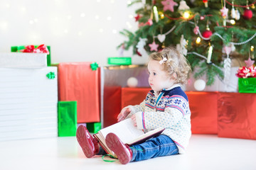 Adorable toddler girl reading book under Christmas tree