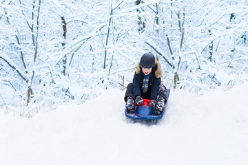 Happy laughing child enjoying sleigh ride in snowy winter park