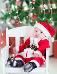 Funny newborn baby boy in Santa outfit under Christmas tree