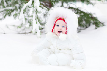 Adorable laughing baby sitting in snow under Christmas tree