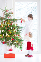 Adorable toddler girl with her brother decorating Christmas tree