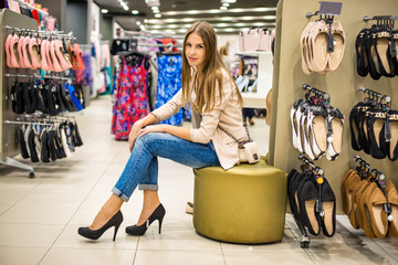 Young and beautiful woman wearing new high heels shoes at shop