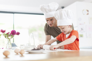 a father and his son preparing a cake in the kitchen