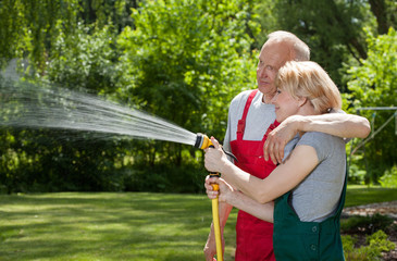 Couple in love watering grass