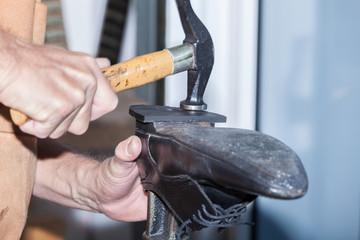 Le cordonnier répare le talon d'une chaussure d'homme