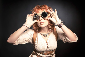 Beautiful redhair steampunk woman looking over her goggles