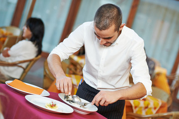 waiter man dressing fish at restaurant