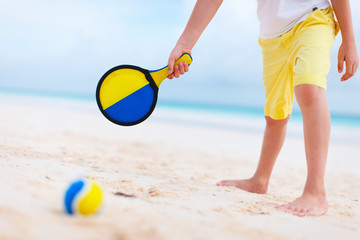 Boy playing beach tennis