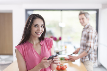 handsome couple in a kitchen, man at work and woman at phone