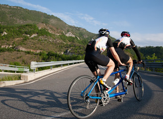 Cyclists on a Tandem bicycle riding uphill on a mountain roadway