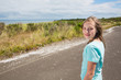 Young girl looking back while traveling on quiet country road