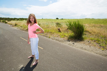 A teenage girl travels barefoot on an empty road