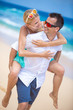 Happy young couple enjoying a solitary beach backriding