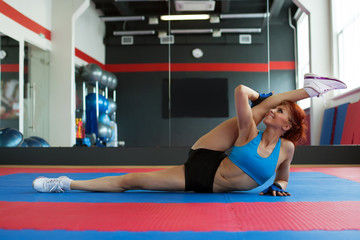 Funny sportswoman stretches at camera in gym