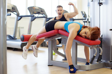 Merry man and woman tired of training in gym