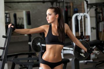 Sexy sportswoman posing on backdrop of simulators