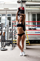 Shapely muscular female athlete posing in gym