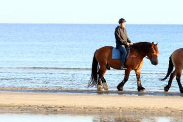Junge mit Pferd reitet am Strand entlang