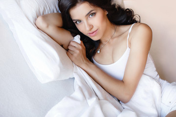Portrait of a young woman lying in bed.