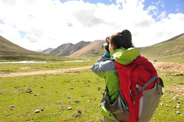 hiking woman taking photo in tibet,china