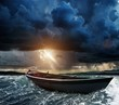 Wooden boat in a stormy sea - 69189111