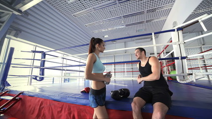 Girl athlete and fitness instructor talking and smiling to each