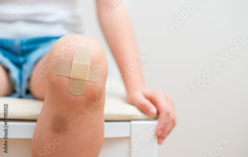 Child knee with an adhesive bandage and bruise. - 69190352