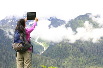 woman hiker taking photo with digital tablet in tibet