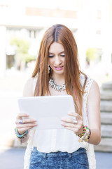 Beautiful young woman holding and looking tablet compuer in the