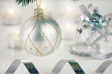 white christmas ball hanging on fir tree