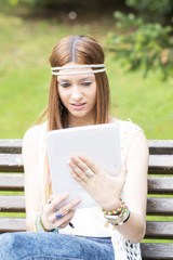 Young beautiful woman looking message in tablet computer, outdoo